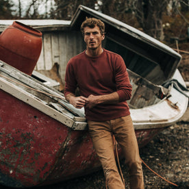 fit model wearing The Crewneck in Brick Red Terry, leaning against boat