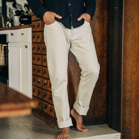 fit model wearing The Democratic Jean in Natural Organic Selvage, cuffed barefoot, hands in pockets