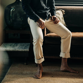 fit model wearing The Democratic Jean in Natural Organic Selvage, cuffed, sitting inside of house