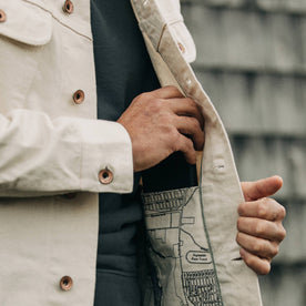 fit model wearing The Long Haul Jacket in Natural Organic Selvage, putting phone in pocket, detail shot