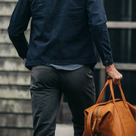 fit model wearing The Morse Pant in Charcoal Slub Linen, back shot holding bag