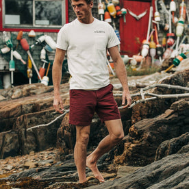 fit model wearing The Morse Short in Brick Red Slub Linen, barefoot on rocks