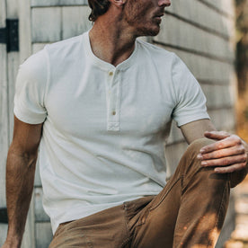 fit model wearing The Short Sleeve Heavy Bag Henley in Natural, sitting, with chore pants on