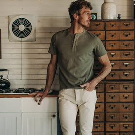 fit model wearing The Short Sleeve Heavy Bag Henley in Washed Olive, next to stove