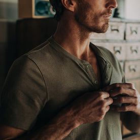 fit model wearing The Short Sleeve Heavy Bag Henley in Washed Olive, cropped of chest