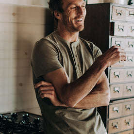 fit model wearing The Short Sleeve Heavy Bag Henley in Washed Olive, laughing
