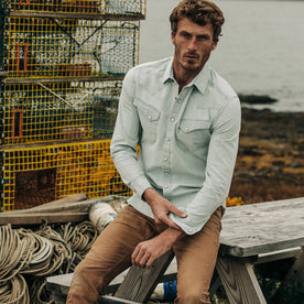 fit model wearing The Western Shirt in Washed Selvage Chambray, sitting on bench