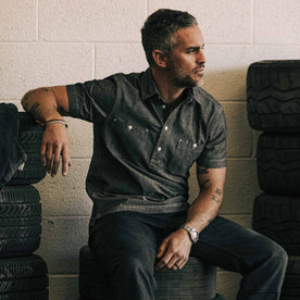our fit model wearing The Short Sleeve Popover in Charcoal Chambray—sitting in the garage