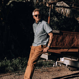 our fit model wearing The Short Sleeve Popover in Blue Chambray—looking left against a truck