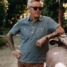 our fit model wearing The Short Sleeve Popover in Blue Chambray—looking left, shoulder on truck