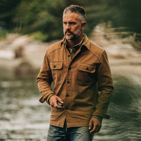 our fit model wearing The Shop Shirt in British Khaki Boss Duck—near a creek