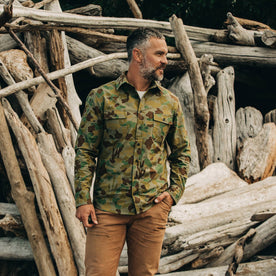 our fit model wearing The Yosemite Shirt in Arid Camo—on a beach, looking right