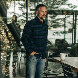 our fit model wearing The Yosemite Shirt in Blackwatch Plaid—drinking coffee at a cabin