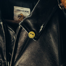 material shot of The All Smiles Enamel Pin on jacket