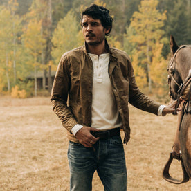 fit model wearing The Bomber Jacket in Field Tan Wax Canvas, with horse