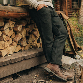 fit model wearing The Camp Pant in Dark Moss Wool, sitting against some logs