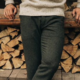fit model wearing The Camp Pant in Dark Moss Wool, sitting against wood