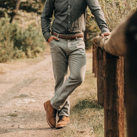 fit model wearing The Camp Pant in Heather Grey Wool—hand on wood fence
