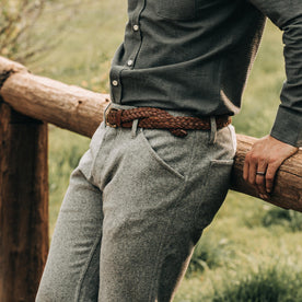 fit model wearing The Camp Pant in Heather Grey Wool—sitting on fence