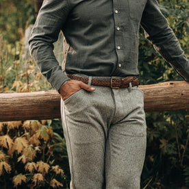 fit model wearing The Camp Pant in Heather Grey Wool—resting against fence