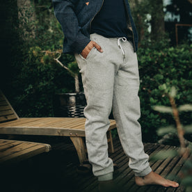 our fit model wearing The Heavy Bag Pant in Heather Grey Fleece with both hands in pocket on a deck