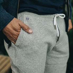 our fit model wearing The Heavy Bag Pant in Heather Grey Fleece closeup with right hand in pocket showing TS embroidered logo