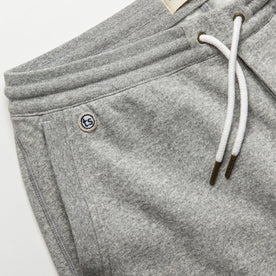 material shot of The Heavy Bag Short in Heather Grey Fleece with left side pocket visible with TS embroidered logo
