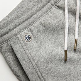 material shot of The Heavy Bag Short in Heather Grey Fleece with TS embroidered logo visible above right side hand pocket