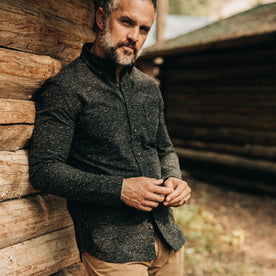 our fit model wearing The Jack in Coal Donegal—leaning against cabin