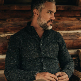 our fit model wearing The Jack in Coal Donegal—sitting, looking right next to cabin