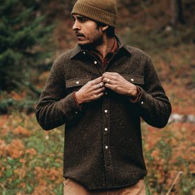 our fit model wearing The Leeward Shirt in Olive Donegal playing with buttons on placket in wildflower field