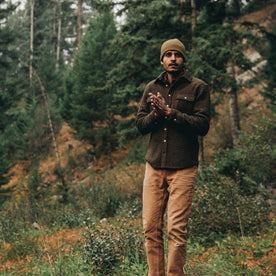 our fit model wearing The Leeward Shirt in Olive Donegal standing in a field with entire shirt visible in front of a forrest