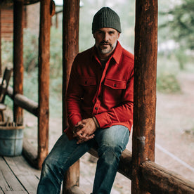 our fit model wearing The Maritime Shirt Jacket in Clifford Red—sitting, hands clasped