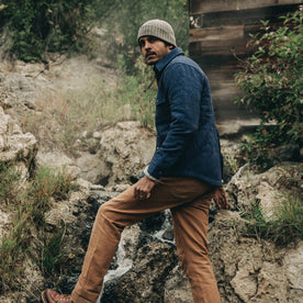 fit model wearing The Quilted Jacket in Indigo Boss Duck, standing on rocks