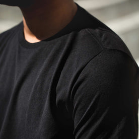 Detail shot of James wearing the black tee
