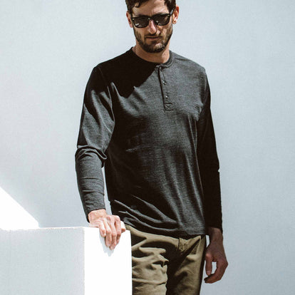 Our fit model wearing the Zaha Henley in Heather Black from Taylor Stitch.