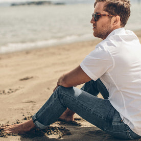 Garrett sitting on the beach in the 24 Month Wash Slim cut denim