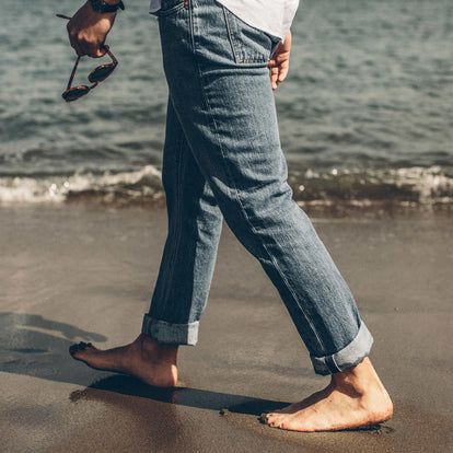 Our fit model walking along the sea shore in twenty-four wash slim cut denim jeans