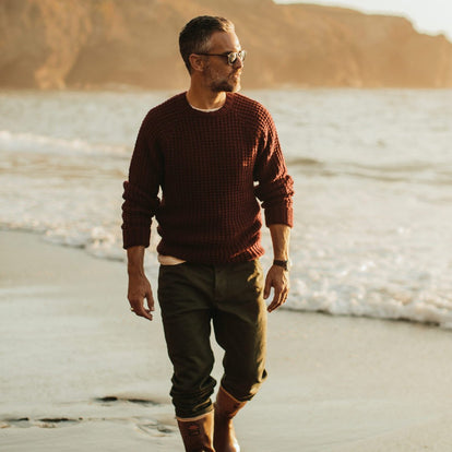 Our fit model in the Fisherman Sweater in Maroon Waffle walking along the beach.
