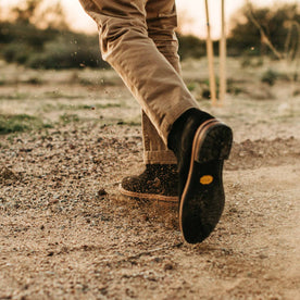 our fit model wearing The Ranch Boot in Coal Weatherproof Suede—kicking up dirt