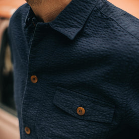 our fit model wearing The Caravan Shirt in Navy Seersucker—cropped shot of chest