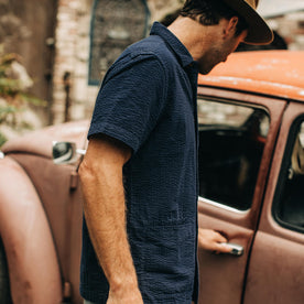 our fit model wearing The Caravan Shirt in Navy Seersucker—cropped shot near car