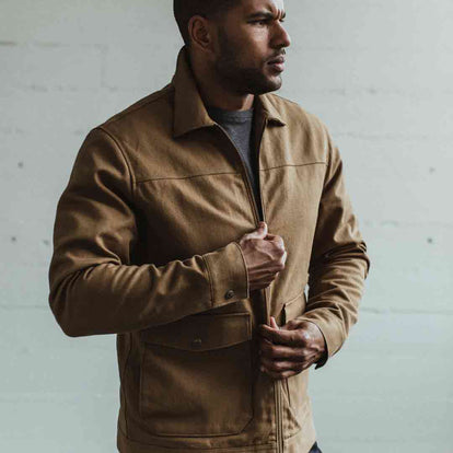Our fit model wearing the Mechanic Jacket in British Khaki Boss Duck sitting next to the river at Sea Ranch California.