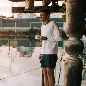 fit model wearing The Heavy Bag Long Sleeve in Natural, holding coffee near water