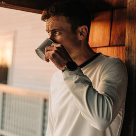fit model wearing The Heavy Bag Long Sleeve in Natural, drinking coffee cropped