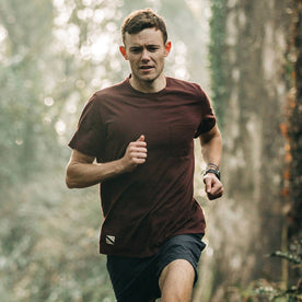 fit model wearing The Merino Tee in Wine, running in woods