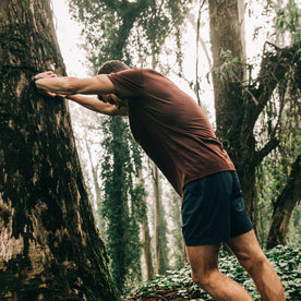 fit model wearing The Merino Tee in Wine, stretching against tree