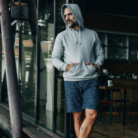 our fit model wearing The Après Short in Indigo Slub—wearing a hoodie early in the morning