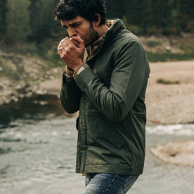 our fit model wearing The Harris Jacket in Forest Dry Wax—walking near creek