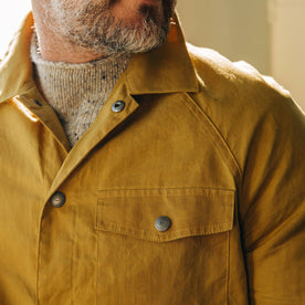 our model wearing the The Lombardi Jacket in Mustard Dry Wax in the studio looking left in a cropped image